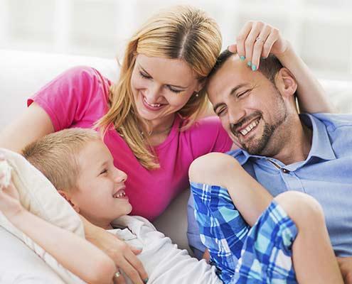 Familie sitzt nach JOYA Massage entspannt zusammen auf der Couch