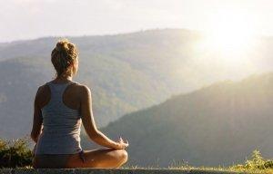 Junge Frau meditiert vor wundervoller Naturkulisse, Foto zum Blogeintrag über Yoga bei JOYA International Massageprodukte