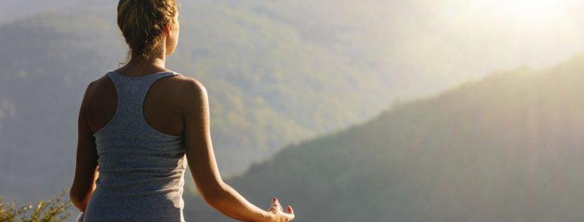 junge Frau meditert vor wundervoller Naturkulisse, Foto zum Blogeintrag bei JOYA International über YOGA