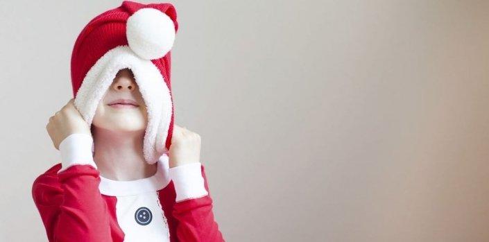 Kind zieht sich Weihnachtsmütze über den Kopf- zu viel gegessen, gehört oder ist ihm alles zu viel?