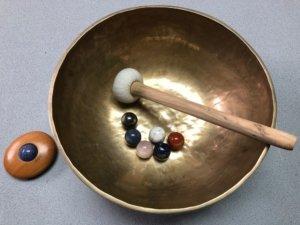 Die Edeslteine in eine Klangschale legen und schwingen lassen zum Entladen der Steine